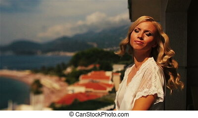 Charming blond bride in white robe shakes her long beautiful hair with the Sveti Stefan in Montenegro, Budva on background