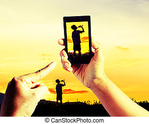 Taking pictures Children playing in sunset, silhouette, freedom and happiness with mobile phone in the blur nature background.