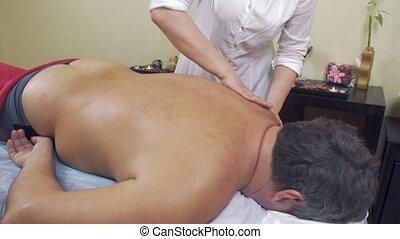Masseuse rubdown neck of adult fat man. Therapeutic massage....