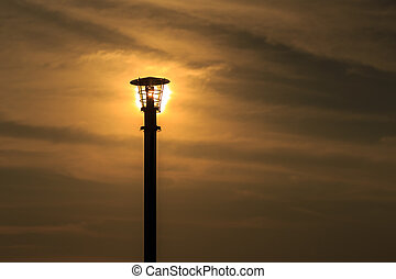 Silhouette of lamp pole on sun and sky background