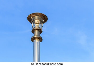 Stainless steel lamp pole at the road on blue sky background