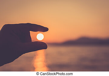 Silhouette of hand with sign on sun