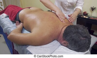 Masseuse press shoulders, backbone of fat man. Therapeutic...