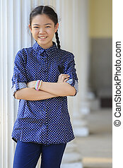 portrait of thai 12s years girl wearing blue shirt standing...