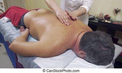 Masseuse press backbone of adult fat man. Therapeutic massage. Medium shot