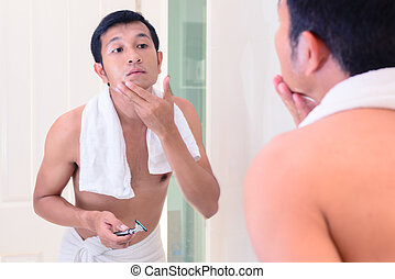 Young handsome man touching his smooth face after shaving...