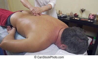 Masseuse hands press backbone of adult fat man. Remedial massage. Medium shot