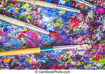 Paintbrush on tray with colorful paint spot on the surface -...