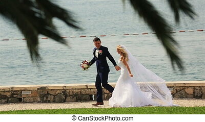 Happy wedding couple running and laughing on beach in...