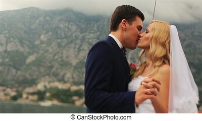 Beautiful wedding couple tenderly kissing on the yacht with...