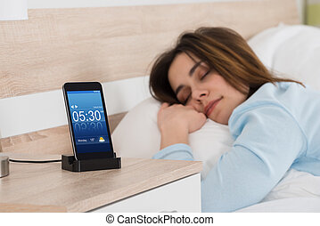 Woman Sleeping On Bed With Alarm On Mobile Phone - Young...
