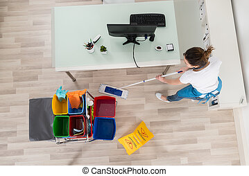 Young Female Janitor Mopping Wooden Floor With Caution Sign