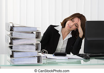 Stressed Businesswoman Looking At Stack Of Folders -...