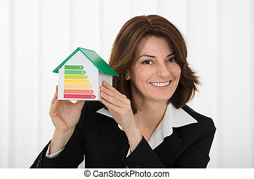 Businesswoman Holding House Model With Energy Efficiency Rate