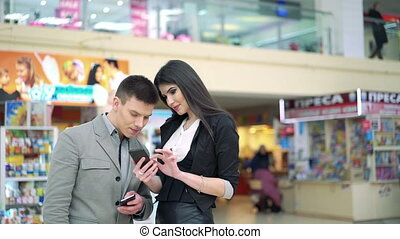 Young people with phones in a trade center - Lovely couple...