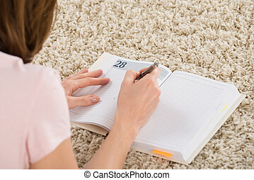 Woman Writing Schedule In Her Diary - Close-up Of Woman...