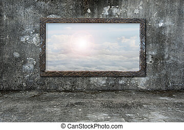 Old wooden frame window on wall with sun clouds sky