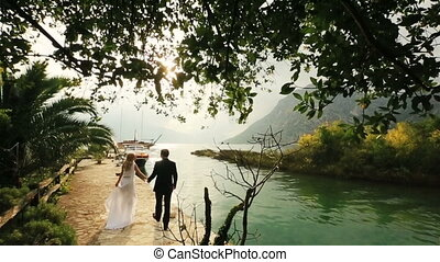 Happy wedding couple walking together on the old quay in Montenegro, Budva with sea and mountains on background
