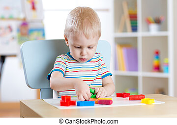 Little boy learning to use colorful play dough in nursery...