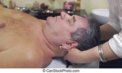 Close up of masseuse hands make healing massage of head to adult fat man.