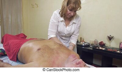 Masseuse hands make professional massage of right hand to adult fat man.