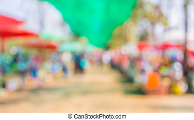 Blurred image of people walking at day market - Blurred...