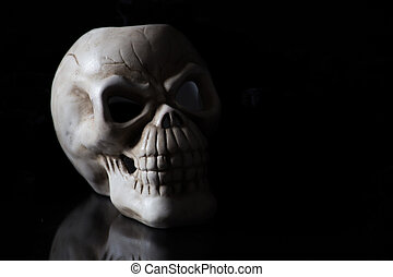 shadowy skull on black - a creepy skull side lit with...