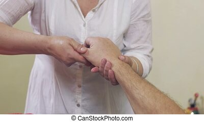 Close up of masseuse hands make massage of hand fingers to adult man. Healthcare