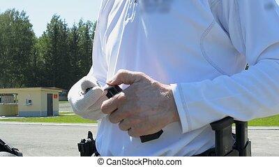 Man loading a handgun - Man charging a handgun gun outside,...