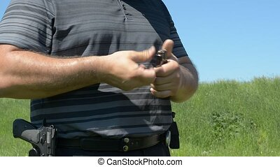 Man loading a handgun gun - Man charging a handgun gun...