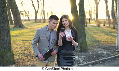 Walking in the park by colleagues with smartphone
