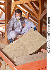 Installing thermal insulation layer on a house - worker...