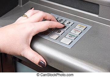 woman's hand entering PIN code on ATM machine