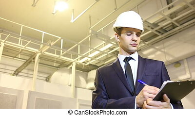 man in business suit and helmet. inspects premises. consults...