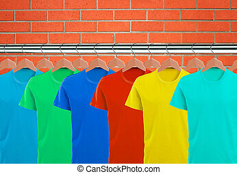 Lots of T-shirts on hangers over orange brick wall