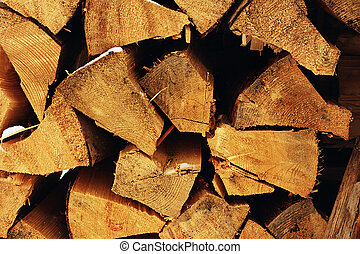 The stack of the snowy firewood on old wooden background....
