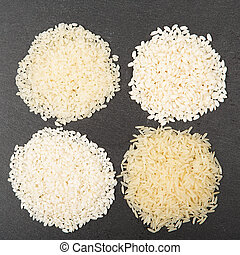 Various color and shape varieties of rice on black slate...