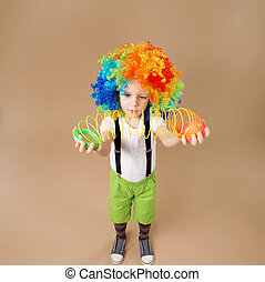 Little boy in clown wig plays with a spring.