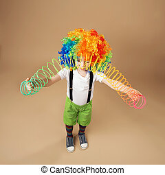 Little boy in clown wig playing with a spring