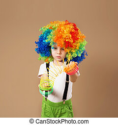 Little boy in clown wig playing with a spring.