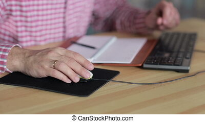 man working with a computer mouse at the table