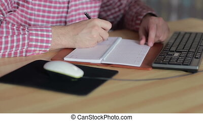 man sitting at the computer and write in the diary -...