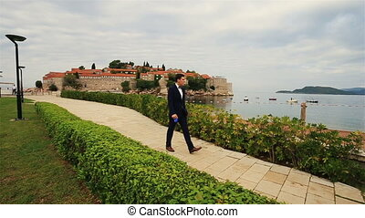 Handsome groom walking the dog on sunny green alley in Montenegro, Budva