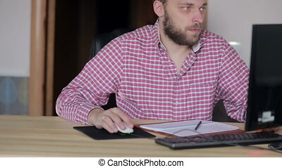 man working at a computer in a home office - middle-aged man...