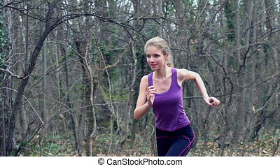Woman runner is jogging on forest path in park. - Sport girl...