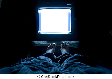 Television Addict - Person watches TV at night in his bed...