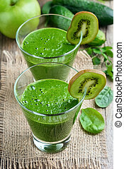 Green smoothie in glasses on rustic table