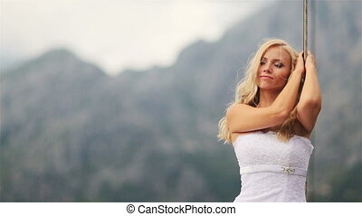 Charming blond bride with eyes closed posing on the stern of...