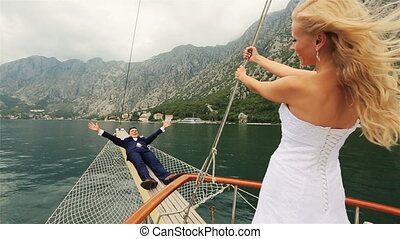 Happy wedding couple having fun on the stern of the ship -...