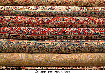 Rolled-up turkish or persian carpets in a variety of colors...
